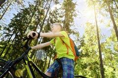 O adolescente feliz monta uma bicicleta na madeira de pinho, no dia ensolarado Fotografia de Stock