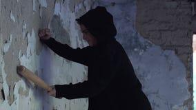 O adolescente irritado que bate a parede com bastão de beisebol, sente desesperado, desespero filme