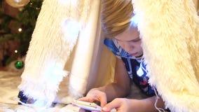 O adolescente joga no smartphone na sala de crianças em uma barraca com uma luz de Natal Infância feliz vídeos de arquivo