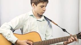 O adolescente joga uma guitarra acústica Na perspectiva da parede leve filme