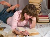 O adolescente lê livros imagens de stock royalty free