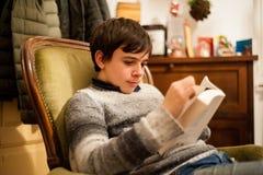 O adolescente lê um livro na poltrona em casa Imagens de Stock