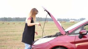O adolescente louro fino retira o medidor de óleo do óleo em seu motor de automóveis para verificar o nível do lubrificante filme
