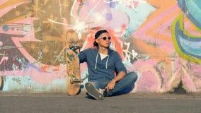 O adolescente masculino está sentando-se perto de uma parede dos grafittis com seu skate video estoque