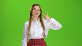 O adolescente mostra os polegares acima Tela verde filme