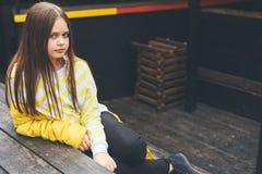 O adolescente na camiseta amarela e em calças de brim pretas senta-se em uma estrutura de madeira foto de stock royalty free