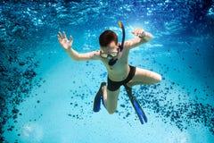 O adolescente na máscara e o tubo de respiração nadam debaixo d'água. Imagem de Stock