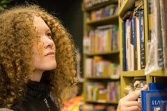 o adolescente novo escolhe um livro na loja fotografia de stock royalty free