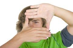 O adolescente olha através de uma estrutura das mãos imagens de stock