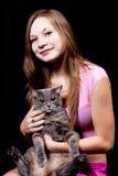 O adolescente prende nas mãos do gato cinzento grande Fotografia de Stock