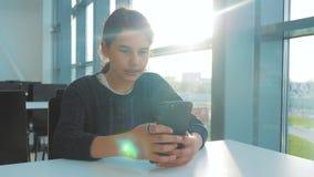 O adolescente que a menina está conversando comunica-se no mensageiro em um smartphone em um café em uma luz solar da tabela teen vídeos de arquivo
