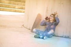O adolescente que senta-se com o filtro morno dos tons do telefone esperto aplicou-se Foto de Stock Royalty Free