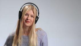 O adolescente que veste fones de ouvido escuta a música video estoque