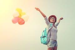 O adolescente que veste os vidros, guardando balloons o ombro colorido Imagem de Stock