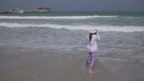 O adolescente toma imagens das ondas do mar do Golfo Pérsico no smartphone na praia do vídeo da metragem do estoque de Dubai vídeos de arquivo