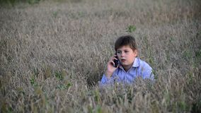 O adolescente usa um smartphone no prado no filme