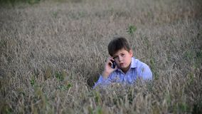 O adolescente usa um smartphone no prado no vídeos de arquivo