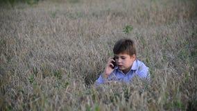 O adolescente usa um smartphone no prado no video estoque