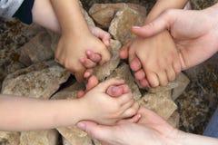 O adulto e chilcren o círculo de pedra das mãos da terra arrendada Fotos de Stock Royalty Free