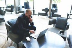O advogado bem sucedido masculino está estudando negociando o cliente novo usando o rede-livro, quando se sentar no café fotos de stock
