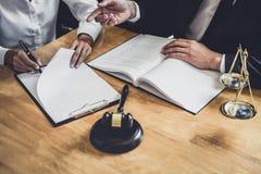 O advogado ou o conselheiro masculino que trabalham na sala do tribunal t?m a reuni?o com cliente s?o consulta com pap?is do cont foto de stock