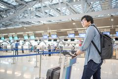 O aeroporto de espera do homem asiático novo verifica dentro Fotos de Stock Royalty Free