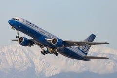 O aeroporto internacional de partida de United Airlines Boeing 757 Los Angeles com neve tampou montanhas no fundo fotografia de stock royalty free