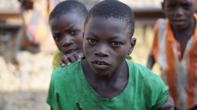 O africano editorial da foto privou a criança que espreita através das janelas de um trem de passageiros, fotografadas em outubro imagens de stock royalty free