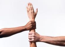 O africano negro americano e as mãos caucasianos que guardam a pele branca armam-se na unidade do mundo fotografia de stock royalty free