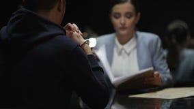 O agente da autoridade que faz perguntas apronta o suspeito de assassinato na sala escura video estoque