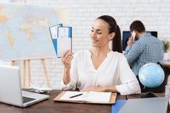 O agente de viagens mantém bilhetes para o plano na agência de viagens Fotos de Stock Royalty Free
