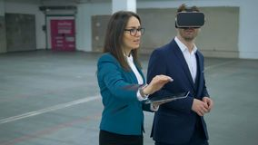 O agente imobiliário fêmea está mostrando um salão vazio a um homem de negócios nos VR-vidros Bens imobiliários comerciais vídeos de arquivo