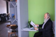 O agente masculino do banqueiro ou do dinheiro na idade avançada resolve o issu importante do trabalho Fotografia de Stock