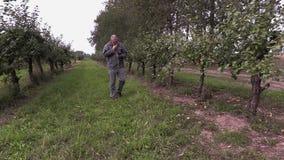 O agrônomo anda através do pomar de maçã filme