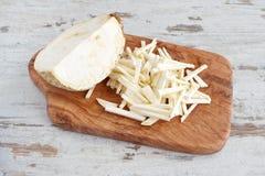 O aipo de raiz cortou em partes pequenas com a metade da raiz de aipo inteira em uma placa de corte de madeira verde-oliva em um  Imagem de Stock