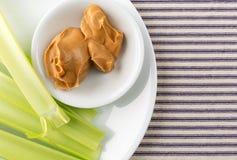 O aipo desengaça com manteiga de amendoim em uma placa branca Fotos de Stock Royalty Free