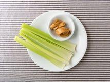 O aipo desengaça com manteiga de amendoim em uma placa branca Fotografia de Stock Royalty Free