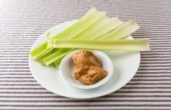 O aipo desengaça com manteiga de amendoim em uma placa branca Foto de Stock