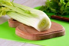 O aipo desengaça na placa e na faca da cozinha Imagem de Stock