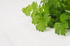 O aipo novo verde sae na placa de madeira branca, espaço da cópia Imagem de Stock