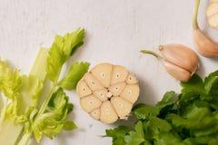 O aipo verde fresco provem no close up de madeira da placa de corte salsa e alho do aipo cozinhando o alimento Copie o espaço, vi Imagens de Stock