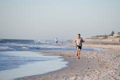 O ajuste atlético e o corredor forte equipam o treinamento na praia do por do sol do verão no corredor da costa de mar e no exerc imagem de stock