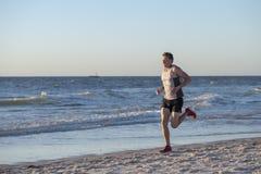 O ajuste atlético e o corredor forte equipam o treinamento na praia do por do sol do verão no corredor da costa de mar e no exerc imagem de stock royalty free