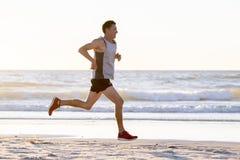 O ajuste atlético e o corredor forte equipam o treinamento na praia do por do sol do verão no corredor da costa de mar e no exerc fotografia de stock royalty free