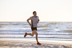 O ajuste atlético e o corredor forte equipam o treinamento na praia do por do sol do verão no corredor da costa de mar e no exerc foto de stock royalty free