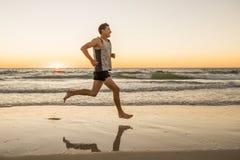 O ajuste atlético e o corredor forte equipam o treinamento na praia do por do sol do verão no corredor da costa de mar e no exerc fotografia de stock