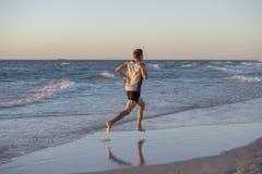 O ajuste atlético e o corredor forte equipam o treinamento na praia do por do sol do verão no corredor da costa de mar e no exerc fotos de stock