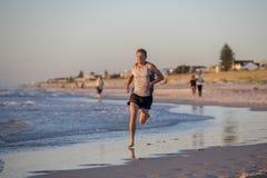 O ajuste atlético e o corredor forte equipam o treinamento na praia do por do sol do verão no corredor da costa de mar e no exerc imagens de stock royalty free