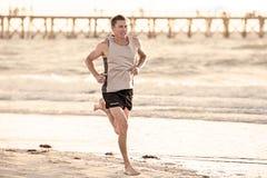 O ajuste atlético e o corredor forte equipam o treinamento na praia do por do sol do verão no corredor da costa de mar e no exerc fotos de stock royalty free