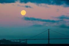 O ajuste da Lua cheia atrás de golden gate bridge e a névoa imediatamente antes do nascer do sol Imagens de Stock